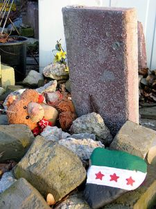 360px-2013-03-02_Gravestone_without_name_fallen_teddy_bear_symbolising_child_and_children_killed_by_war,_stone_with_painted_syrian_flag